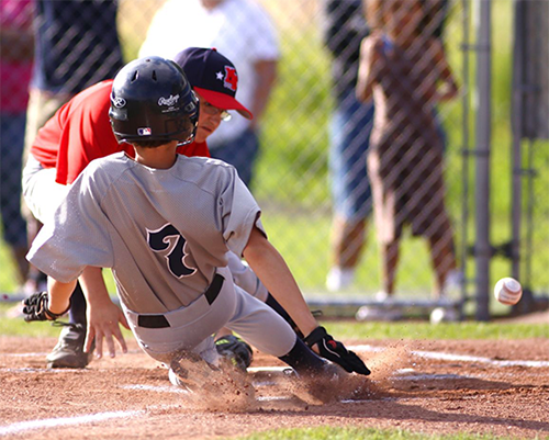 Young baseball player sliding into home plate
